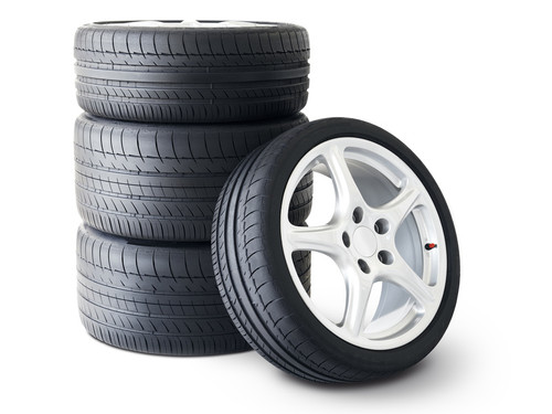 Isolated set of low profile summer tyres with one wheel in front